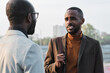 Horizontal over-the-shoulder shot of handsome young African American man standing in front of his co-worker discussing something during break
