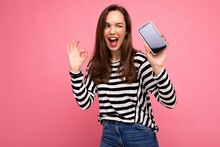 Photo Of Winking Beautiful Happy Young Woman Wearing Striped Sweater Isolated Over Background With Copy Space Showing Ok Gesture Looking At Camera Showing Mobile Phone Screen