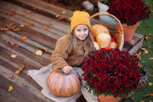 Happy Little Girl Sitting On Porch Of House With Chrysanthemums Potted And Pumpkins. Home Fall Decoration For Halloween Or Thanksgiving. Smilling Child In Autumn Garden With Yellow Pumpkins And Flower