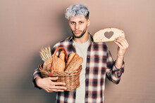 Young Hispanic Man With Modern Dyed Hair Holding Wicker Basket With Bread And Loaf With Heart Symbol Relaxed With Serious Expression On Face. Simple And Natural Looking At The Camera.