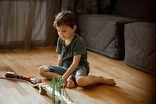 Little Boy 5 Years Old Playing Wooden Railroad At Home. Child Playing With Toys