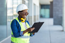 Portrait Of Professional Heavy Industry Female Engineer Wearing Safety Uniform And Hard Hat, Smiling Charmingly. In The Background Unfocused Large Industrial Factory