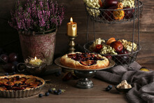 A Seasonal Autumn Fruit Pies And Floral Decoration On The Wooden Table.