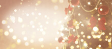 Defocused Holiday Background With Christmas Tree, Balls And Garlands. Beige And Gold Banner With Copy Space And Bokeh