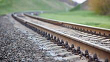 Selective Focus Railway Track Turns And Twists Between Out Of Focus Hills Background. Empty Rounding And Turning Single Track Of Railways. Shallow Focus Perspective Of Rounded Rails Bend Horizontal.
