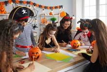 Arts And Crafts Studio Teacher Doing Creative Activity With Kids. Children Dressed Up As Pirates, Witches And Vampires Having Fun Halloween Party With Their Young English Tutor At After School Club
