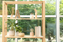 Wooden Shelving Unit With Beautiful Houseplants, Books And Air Reed Freshener Indoors