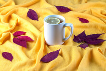 Autumn Composition Of Red Dry Leaves Laid Out On A Bright Yellow Crumpled Cloth And A Ceramic Mug With Hot Tea With Lemon. Selective Focus.