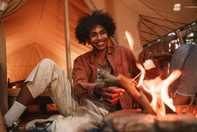 Hansome Young Curly African Man Roasting Marshmallows On Skewers Over Fire Pit At Campsite, Enjoying Outdoor Glamping Holiday With Friends Togetherness Reopen After Pandemic Lockdown.