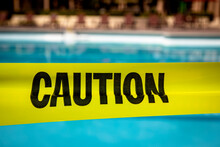 Yellow Caution Tape At A Resort Style Pool Preventing Access Or Use Of The Pool For Contamination Or An Investigation