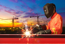 Industrial Welder Welding I Beam Steel Structure Construction By Metal Arc Welding Against Construction Site In Sunset Sky