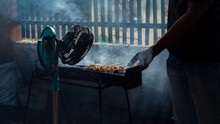 Chicken Satay On Traditional Charcoal Fire. Satay On Fire With Smoke And An Appetizing Look. Hands Cooking Satay On The Grill
