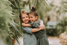 Portrait Of Two Charming Smiling Girls Belonging To Different Races Surrounded By Tropical Leaves. Friendship, Linen Clothing, Environmental Friendliness. High Quality Photo