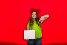 A Girl With A Red Bow On Her Head In A Light Green T-shirt In Blue Jeans Holds A White Sheet Of Paper