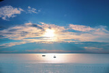 Fototapeta Kawa jest smaczna - Mesmerizing, beautiful morning Mediterranean seascape with turquoise skies, soft sun peeping through the pink clouds and silvery water surface at dawn.