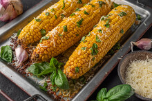 Grilled Corn On The Cob With Butter, Parmesan Cheese And Basil On Baking Sheet. Close Up