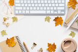 Autumn desk with keyboard, coffee cup, notebook, maple leaves decor on white background. Top view, flat lay home office table, feminine workspace