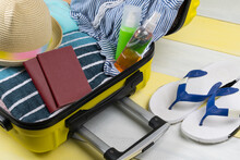 On A Yellow-gray Background, An Open Suitcase For Traveling And A Set Of Items For Recreation In It, A Towel, A Swimsuit, A Hat, Sunscreen And Passport Documents, Next To Flip-flops