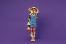 Full Body Young Woman With Halloween Makeup Mask Wearing Straw Hat Scarecrow Costume Hold Jack-o'-lantern Pumpkin Try Hear Overhear Isolated On Plain Dark Purple Background Studio Celebration Concept.