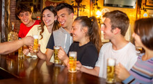 Group Of Millennials Happy Friends Drinking And Toasting Beer In Irish Bar Restaurant..young Teenagers Having Fun Standing Together In A Vintage Pub Counter. Youth, Joy, Happy Hour Celebration Concept