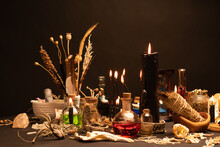 Witchcraft Still Life With Witch Weeds Selective Focus At Front. Esoteric Gothic And Occult Witch Table For Halloween. Various Magic Objects And Ritual Arrangement With Symbols. Gothic Halloween.