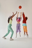 Multiracial friends play basketball game in studio