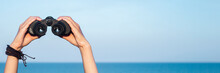 Female Hands Hold Binoculars Against The Background Of The Sky And The Sea. Banner