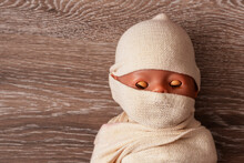 The Doll The Baby Is Wound With Fabric. The Body Of The Child Is Shrouded In A Shroud. The Concept The Muslim Dead Man. A Mummy On A  Background. Close-up. Corpse, Dead. Funeral Concept, Before Burial