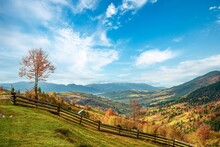 Village Under The Hills Sheltered By Autumn Forests In The Light Of The Bright Sun In Good Weather