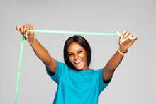 Beautiful Young Black Lady Excitedly Stretching A Measuring Tape Above Her