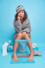 Stunned Asian Woman Dressed In Grey Bathrobe And Sleepmask Sits On Toilet In Lavatory Room Has Diarrhea Problem Defecates At Restroom Poses Against Blue Background. Female Model Has Constipation