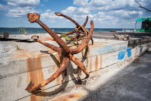 Old Rusty Marine Anchor On The Pier Close Up Background.
