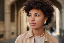 Close Up Shot Of Beautiful Curly Haired Afro American Woman Looks Away Thoughtfully Wears Beige Jacket Earrings Looks Somewhere Poses Against Blurred Background Strolls In City Thinks About Future