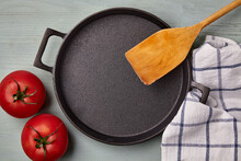 Empty Round Cast Iron Skillet, Wooden Spatula, Tea Towel And Tomatoes