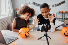 Two Smiling African-American Kids Waving At Smartphone While Video Chatting On Live Streaming On Halloween