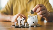 Businessman Putting Coin On The Piggybank And Paper Family On Table, Donation, Saving, Charity, Family Finance Plan Concept, Fundraising, Superannuation, Investment, Financial Crisis Concept.