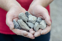 The Man Holds The Rubble In His Palms. Pieces Of Random Granite Stones. Close-up. Selective Focus. Outside The Room.