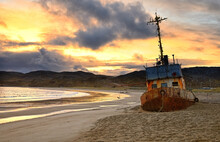 An Old Rusty Longboat Against The Background Of A Fiery Sky At Sunset