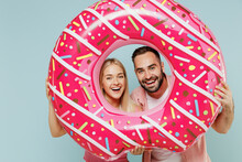 Young Fun Couple Two Friends Family Man Woman In Casual Clothes Looking Through Inflatable Rubber Ring Together Isolated On Pastel Plain Light Blue Background Studio Portrait People Lifestyle Concept.