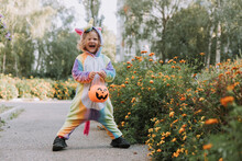Cute Little Girl In A Rainbow Unicorn Costume For Halloween Goes To Collect Sweets In A Pumpkin Basket In A Residential Area. Child Walks In The Outdoor. Trick Or Treat. Lifestyle. Kigurumi