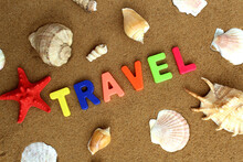 The Word Travel Surrounded By Seashells Is Written In Colored Letters On The Sand.