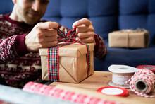 Man Tying Ribbon Bow On Christmas Present At Home