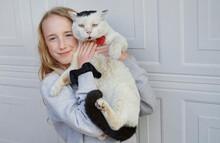 Girl Hugging Cat In Front Of Garage Door