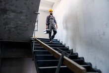 A Bearded Handyman With A Helmet On His Head With A Toolbox In His Hands Is Going Down The Stairs In A New Building In The Building Process. There Is A Lot Of Work To Do.