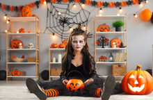 Portrait Of Child In Spooky Costume. Kid Dressed Up For Halloween Party At Home. Girl Wearing Black Dress, Witch Hat And Scary Makeup Sitting On Floor In Room Decorated With Pumpkins And Spider Webs