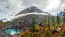 Panoramic View Of The Autumn Mountain, A Narrow Strip Of Fog Over The Mountain Slopes In The Distance, White Clouds Filling The Mountain Gorge. A Clear Blue Mountain Lake And A Bright Autumn Forest.