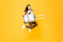 Energenic Beautiful Asian Woman Tourist With Luggage Jumping In Mid-air Isolated On Yellow Studio Background