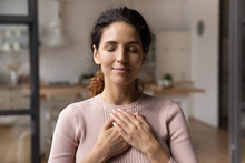Close Up Of Calm Young Caucasian Woman Hold Hands On Heart Chest Feel Grateful And Thankful. Happy Millennial Female Show Gratitude, Love And Care, Pray Or Visualize. Religion, Faith Concept.