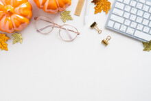Autumn Desk Table With Pumpkins, Keyboard, Glasses On White Background. Blogger Workspace Top View. Flat Lay. Cozy, Hygge Style Workplace.