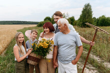 Multi-generational Family With Tansy Flowers And Gardening Equipment At Agricultural Field